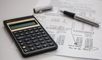 black-calculator-near-ballpoint-pen-on-white-printed-paper-53621-356x210
