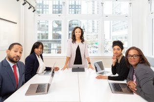 woman-standing-on-the-center-table-with-four-people-on-the-1367271-315x210