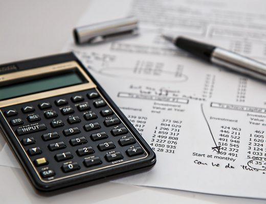 black-calculator-near-ballpoint-pen-on-white-printed-paper-53621-520x400