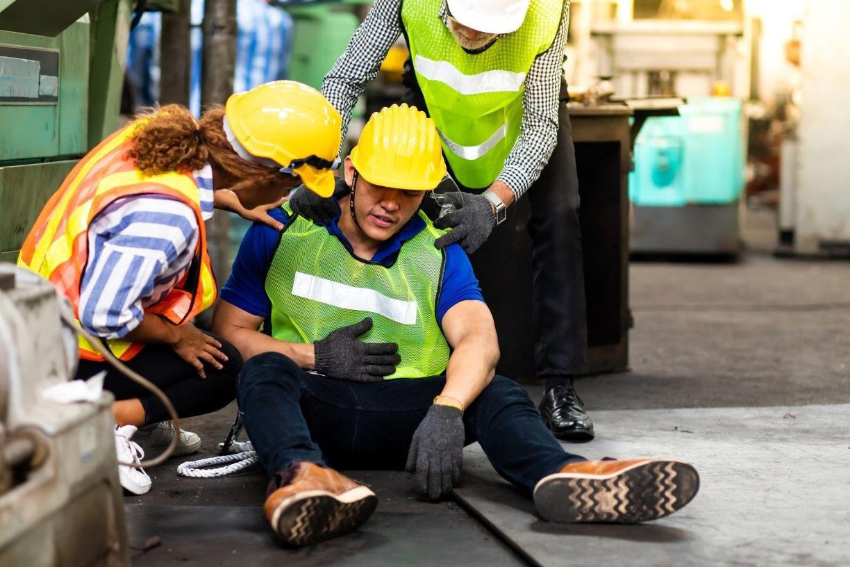 Duas mulheres engenheiras auxiliando trabalhador no chão de fábrica